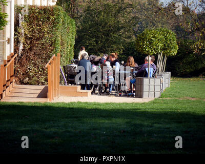 Families eating lunch in Fulham palace restaurant enjoying the last of the sun in October - Stock Image