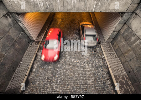 two blurred passanger cars, red and silver, on cobble street in Warsaw, Poland, overhead view - Stock Image