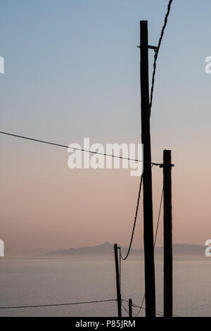 Electric power lines attached to wooden poles with the Saronic Islands and gulf in the background, Saronida, East Attica, Greece, Europe. - Stock Image