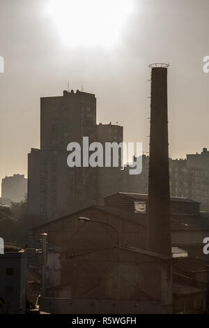 Old brick chimney from an abandoned factory, from the industrial revolution, while an socialist yugoslav housing block building tower can be seen in t - Stock Image