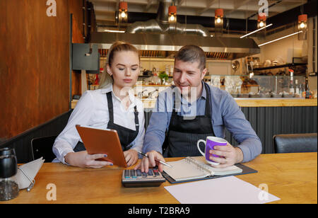 Young woman and her husband sitting at table with tablet and crumpled papers doing accounts for their small restaurant late in evening. Restaurant own - Stock Image