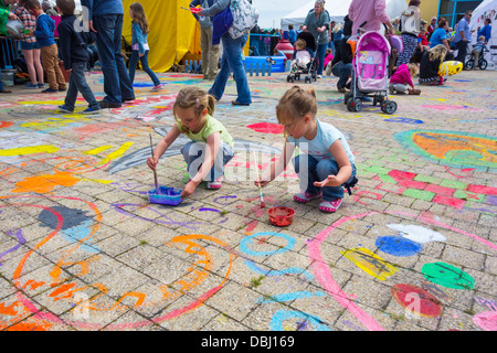 Two young girls doing floor painting at the Pembrokeshire Fish Week festival at Milford Haven. - Stock Image