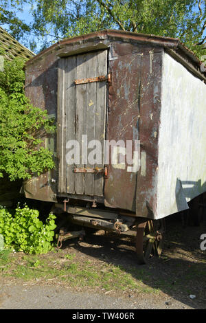 Old wheeled shepherds hut, used for storage in a farm yard. Purbeck, Dorset, UK - Stock Image