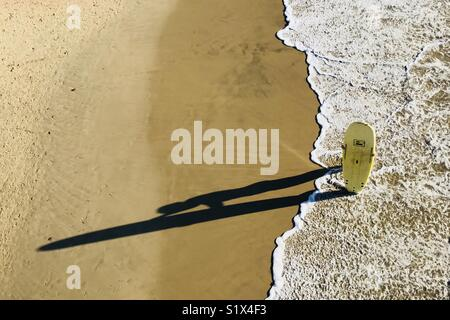 A person holding a surfboard on the beach. Manhattan Beach, California USA. - Stock Image