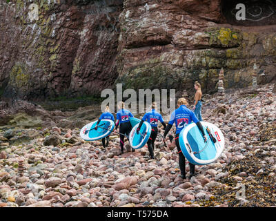 Dunbar, East Lothian, Scotland, UK. 21st Apr 2019. UK Weather:  People enjoy the very sunny hot Easter day weather at Eye Cave cove. A group of paddle boarders walk over the rocky shore to go into the sea for a paddle boarding lesson with Coast to Coast surf school - Stock Image