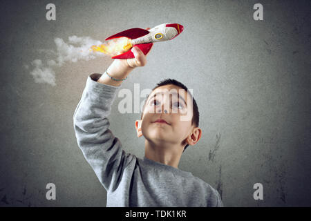 Child plays with a rocket. Concept of imagination - Stock Image