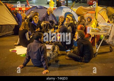 A group of students sit on the road at night at Marble Arch for the Extinction Rebellion demonstration - Stock Image