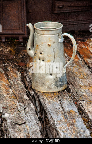 Old tin kettle with bullet holes at abandoned marble quarry, Camp Mansfield, Blomstrandhalvoya, Svalbard Archipelago, Norway - Stock Image