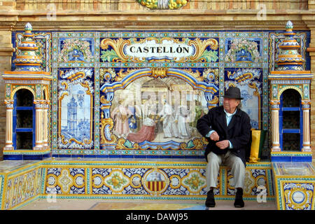 An old man sits on a bench adorned with colourful tiles depicting historical scenes of the respective provinces - Stock Image