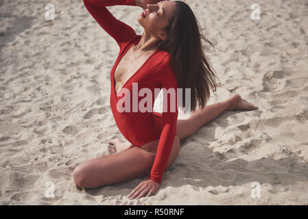 Beautiful young tanned woman in red bikini posing on the beach. Sexy model portrait with perfect body. Summer vacation concept - Stock Image