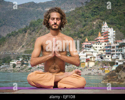 A man practicing yoga by the river Ganges in Rishikesh India - Stock Image