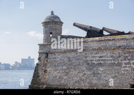 Old rusty cannons perched on Morro Castle point out over Havana Harbour. - Stock Image