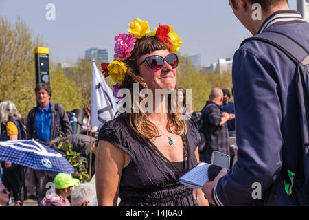 London, UK. 17th April 2019. A woman from XR gives an interview to the press. Two days after Extinction Rebellion closed Waterloo Bridge turning it into a 'Garden Bridge' it remains closed to traffic despite a couple of hundred arrests. Activities continue on the bridge with new protesters arriving. Credit: Peter Marshall/Alamy Live News - Stock Image