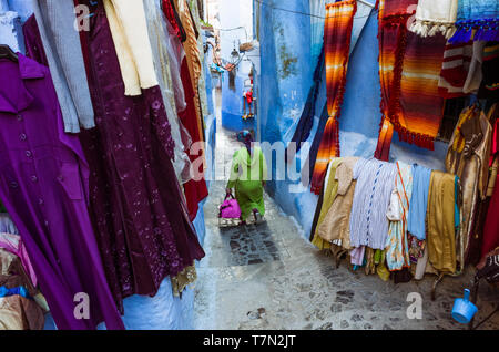 Chefchaouen, Morocco : A woman  walks past a clothing store in the blue-washed medina old town. - Stock Image