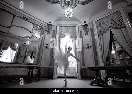 Beautiful ballerina dancing in a luxurious hall with a chandelier and mirrors against the window. Black and white image. - Stock Image