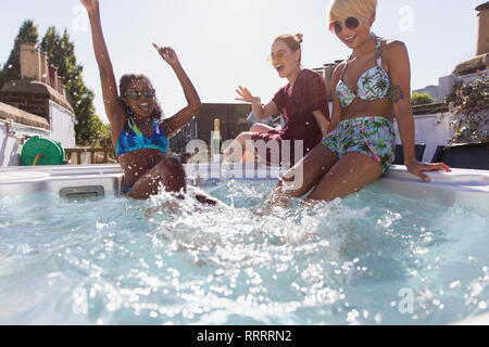 Playful young women friends splashing in sunny hot tub - Stock Image