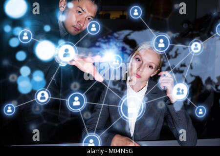 Two business persons in front of futuristic display. Social networking concept. - Stock Image