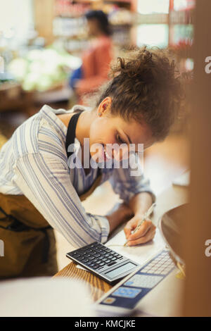 Smiling female cashier using calculator at store counter - Stock Image
