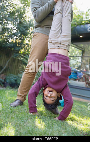 Playful boy hanging upside down in backyard - Stock Image