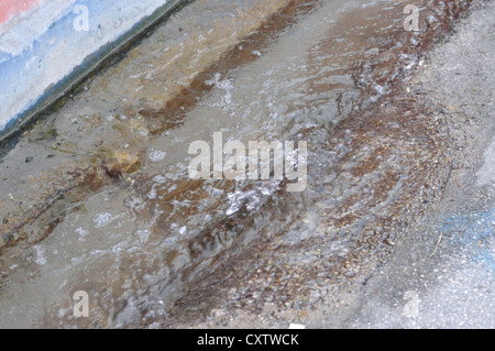 Water puddle near house foundation - Stock Image