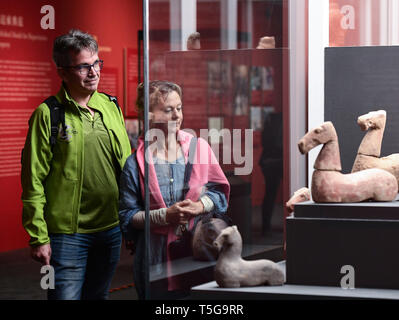 Beijing, China. 24th Apr, 2019. Two foreign visitors view cultural relics at the National Museum of China in Beijing, capital of China, April 24, 2019. Chinese cultural relics returned from Italy are on display at the National Museum of China in Beijing from April 24 to June 30. The exhibition, titled 'The Journey Back Home' showcases more than 700 pieces of returned Chinese artifacts. Credit: Li He/Xinhua/Alamy Live News - Stock Image
