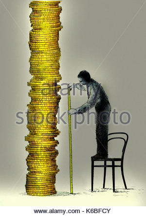 Man standing on chair measuring tall pile of money with tape measure - Stock Image
