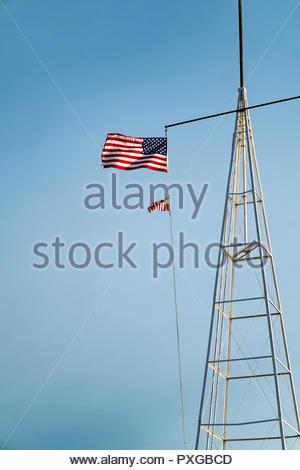 American and U.S. Coast Guard flags fly on radio tower of Coast Guard Station in Grand Marais, Minnesota, USA. - Stock Image