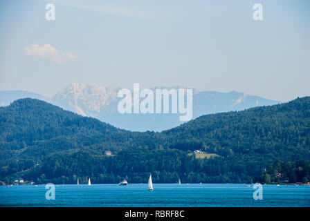 Austria lake Woerther See sail boats on the blue water on a background of forested mountains - Stock Image