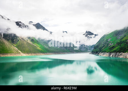 Deep scenic view to alpine lake at high mountains with cloudy sky - Stock Image