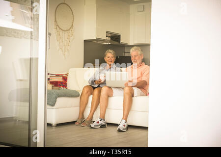 Elderly lifestyle with caucasian old aged mature couple at home sitting on the white sofa and enjoying technology laptop together in relax - senior pe - Stock Image