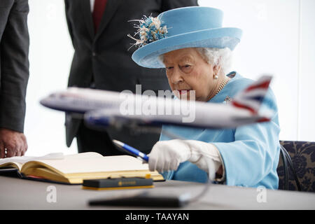 Queen Elizabeth II signs the visitor's book during a visit to the headquarters of British Airways at Heathrow Airport, London, to mark their centenary year. - Stock Image