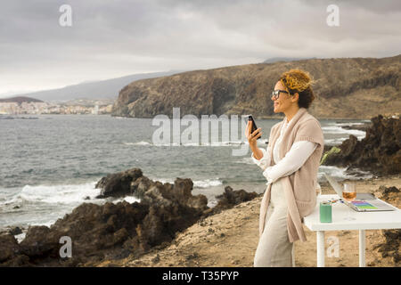 Young happy businesswoman  working outdoor in alternative office enjoying the nature and the ocean breeze - digital nomad concept with nice lady and t - Stock Image