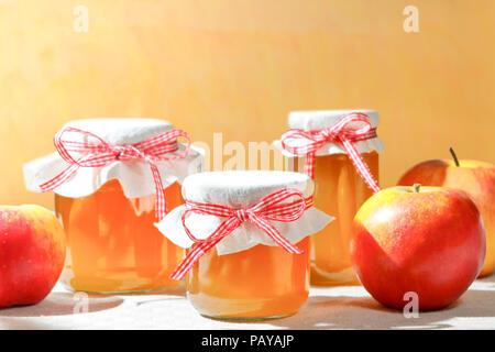 Homemade apple jelly in glass jars with linen cover and a nostalgic ribbon bow in bright sunshine in front of a vintage orange wall, text space - Stock Image