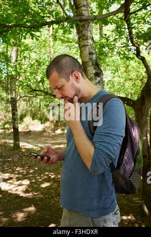 Male hiker looking down at smartphone in forest - Stock Image