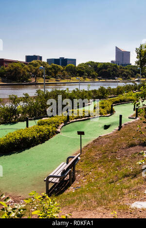 A minature golf course running beside the Arkansas river with city buildings  in background. River Walk on opposite shore. Wichita, Kansas, USA. - Stock Image
