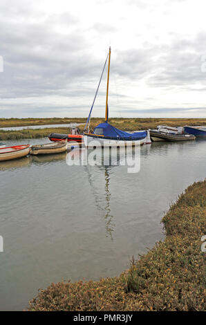 A view of boats moored in the Creek by salt marshes on the North Norfolk coast at Morston, Norfolk, England, United Kingdom, Europe. - Stock Image