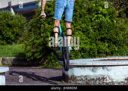 Cyclist on a mountain bike jumping on a stone decoration in the city. - Stock Image