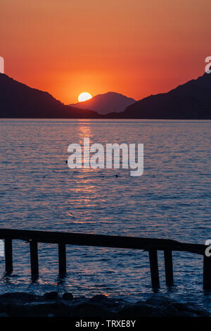 Beautiful sunset at the sea coast. Sun is setting behind the stone and leaving sunlight path over the water. - Stock Image