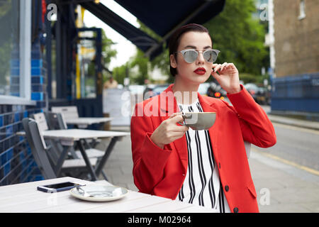 Woman sitting outside cafe drinking coffee - Stock Image