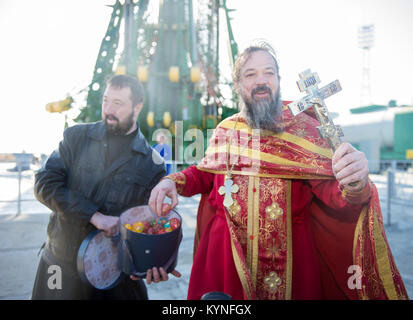 An Orthodox priest hands out Easter eggs to the media at the Baikonur Cosmodrome launch pad after blessing the Soyuz - Stock Image