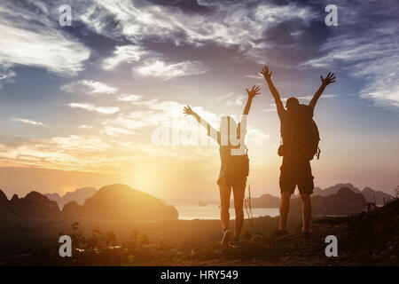 Happy couple stands in winner pose with rised arms on background of sunrise mountains and sea. Success concept - Stock Image