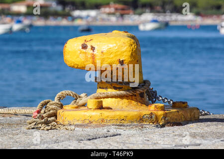 A mooring bollard entwined with a mooring rope. Moored ships at the port quay - Stock Image