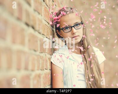 Girl with glasses, Teenager, 12 years, leans against a wall, rain of flowers, Portrait, Germany - Stock Image