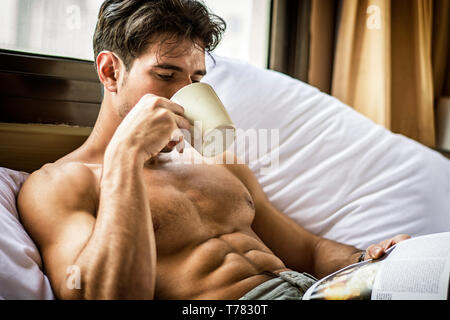 Sexy handsome young man laying shirtless on his bed next to window, holding a coffee or tea cup while reading a book - Stock Image