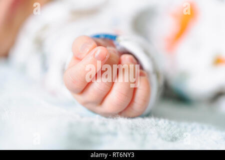 New baby parenthood Mother's Day Fathers Day concept authentic soft focus closeup of a newborn baby boy  hand with a vintage analog Kodachrome feel. - Stock Image