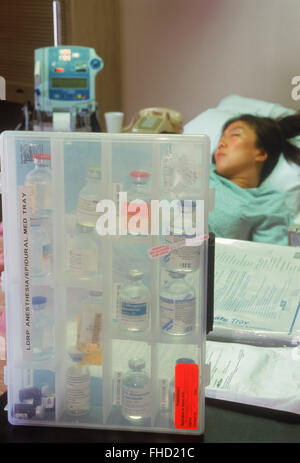 Woman connected to IV tubes in hospital recovery room with a menu of drugs - Stock Image