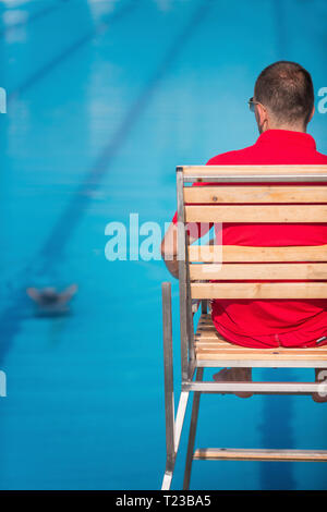Lifeguard in chair, overlooking swimming pool. - Stock Image
