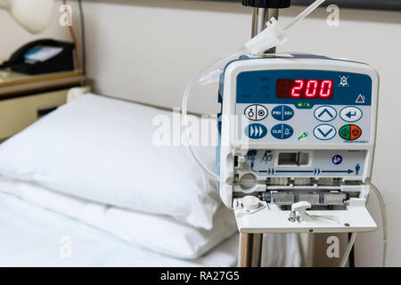 Drip infusion pump in a hospital ward, used to deliver controlled doses of fluids and medicines. - Stock Image