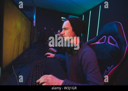 Serious young man in beanie sitting at table and using computer while playing shooter video game - Stock Image