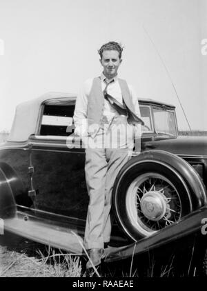 A young man poses on the running board of his automobile, ca. 1932. - Stock Image